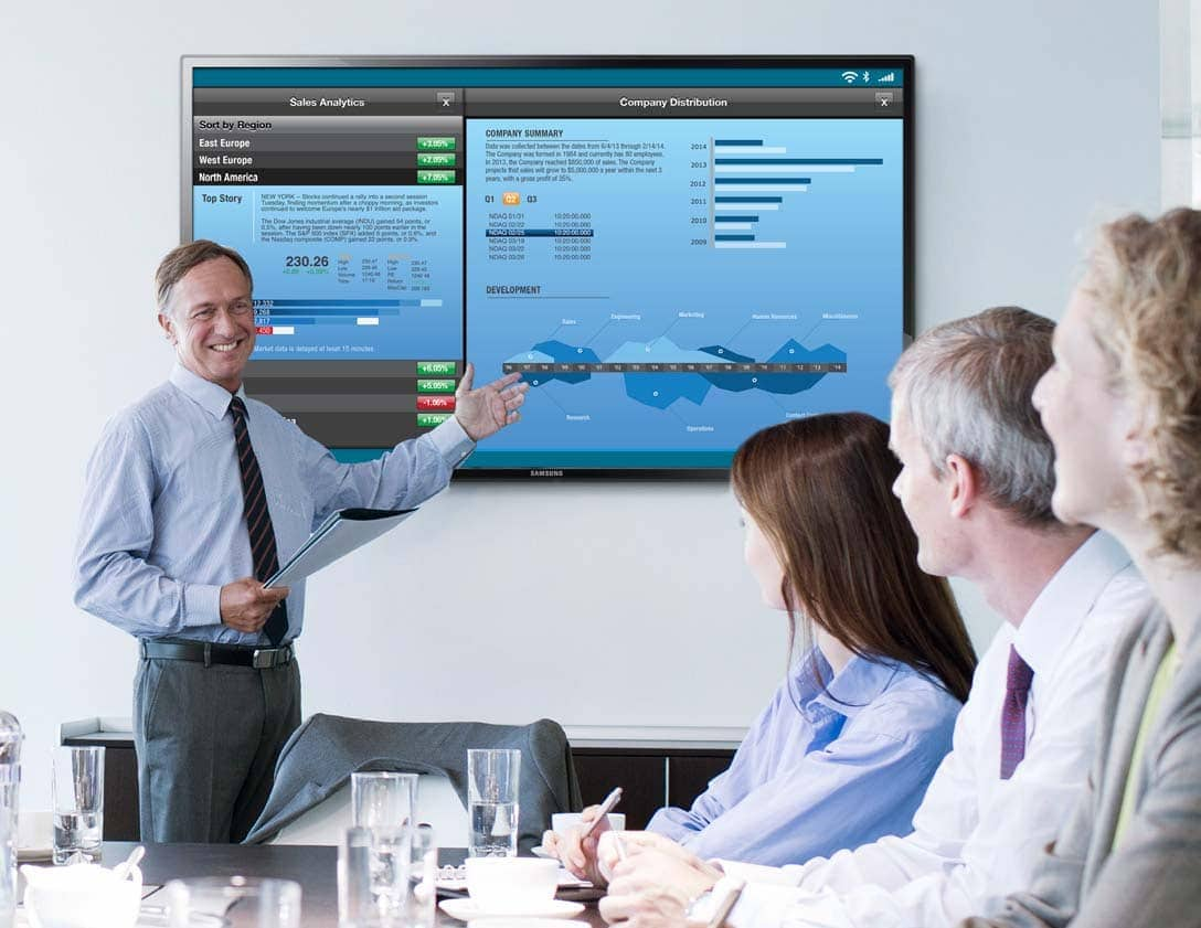 A man giving a presentation to his co-workers on a touch screen monitor