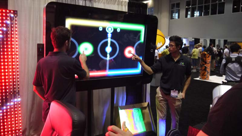 Playing glow hockey on a giant iPhone at IAAPA 2017